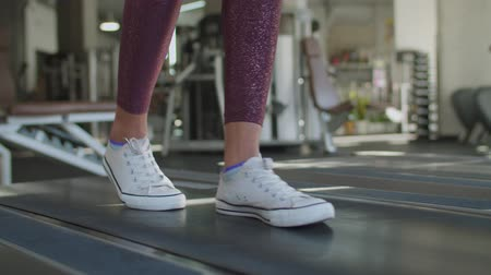 stepping : Close-up of slim female legs in sport shoes and leggings walking on running treadmill machine during cardio workout in fitness club. Womans feet in sneakers stepping on running track at gym. Stock Footage