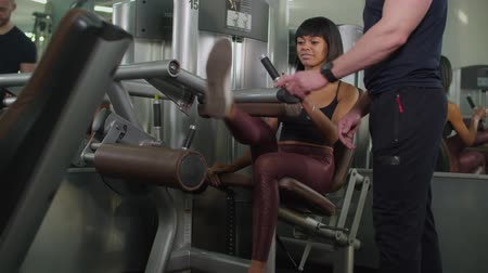 quadriceps : Lovely fit mixed race woman in sportswear doing leg extension workout at exercise machine with personal fitness instructor at gym. Female athlete flexing leg muscles at lever machine in health club.