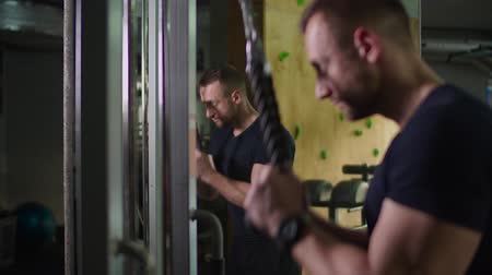 weightlifting : Determined bodybuilder exercising triceps pushdown at rope cable machine during upper-body routine at gym. Concentrated fit man pumping triceps muscles with pulldown ropes fitness equipment machine. Stock Footage