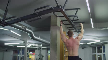 плечо : Shirtless muscular build man doing crossfit training on monkey bars station in health club. Determined bodybuilder flexing shoulder muscles, working on grip strength while exercising on monkey bars. Стоковые видеозаписи