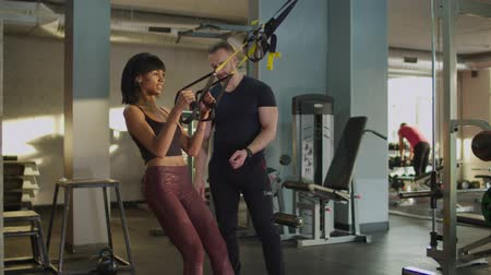 contra : Attractive sporty fit african american woman with perfect body doing suspension training under guidance of personal trainer at gym. Female exercising pull-ups with trx fitness straps in health club. Stock Footage