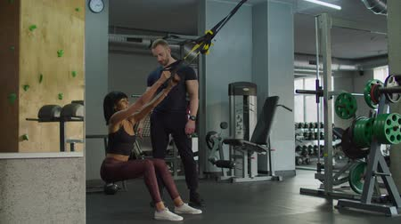 süspansiyon : Determined sporty fit mixed race female exercising for endurance with trx fitness straps with personal trainer at gym. Beautiful woman training upper body on suspension trainer sling in health club.