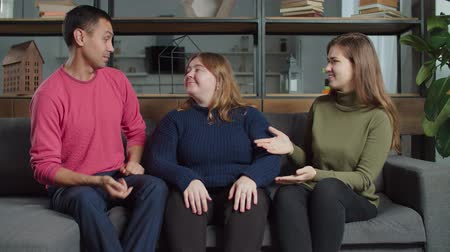 deafness : Handsome hearing impaired man flirting with charming lovely deaf-mute woman using sign language on sofa , arranging romantic date and jealous female friend interrupting them in the middle.