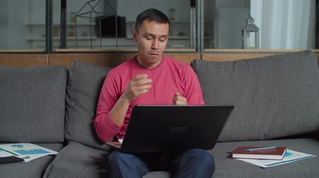 remotely : Deaf-mute male freelancer working on new business startup at home office, video conferencing online with partners on laptop pc talking using sign language, discussing financial charts and data. Stock Footage