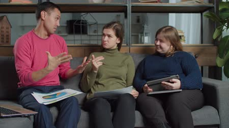 deaf mute : Creative diverse hearing impaired freelancers brainstorming, discussing financial data while working on startup business at home office. Deaf-mute business colleagues planning strategy for new project Stock Footage