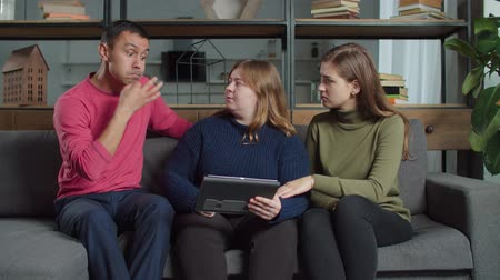 deafness : Positve deaf-mute female friends helping hearing impaired man to make right choice on online dating service using digital tablet. Girlfriends giving advice to guy about partner on online dating app.