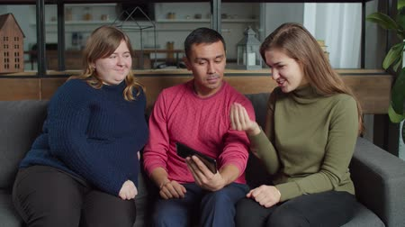 dinleme : Positive diverse hearing impaired friends networking with smart phone and discussing online content using sign language at home. Deaf-mute people browsing social media with cellphone in domestic room. Stok Video
