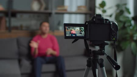 deafness : Close-up of professional video camera on tripod filming positive hearing impaired male blogger in domestic room. Deaf-mute web influencer recording video for vlog using sign language at home. Stock Footage