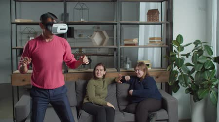 comics : Excited casual man testing virtual reality headset, playing game while deaf-muite female friends watching, laughing and joking using sign language. Cheerful guy getting experience using VR glasses.
