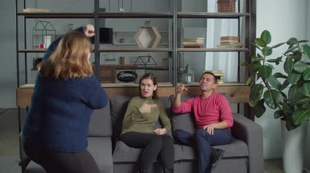 deafness : Cheerful diverse deaf-mute people having fun playing guessing game in domestic room during weekend. Joyful hearing impaired friends trying to guess what deaf female showing in charades at home.