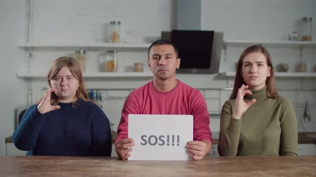 nonverbal : Concentrated diverse deaf people signing words sos and help, written on paper sheet, on sign language in domestic kithen. Positive hearing impaired friends showing words on sign language. Stock Footage