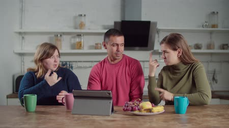 conferencing : Positive deaf diverse people video conferencing online with digital tablet using sign language in domestic kitchen. Hearing impaired friends with tablet pc chatting online using sign language indoors.