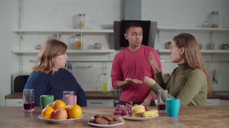 逆境 : Worried deaf man with attractive hearing impaired female friends talking about overdue rental payment using sign language in the kitchen. Diverse deaf-mute roommates arguing about unpaid bills indoors 動画素材