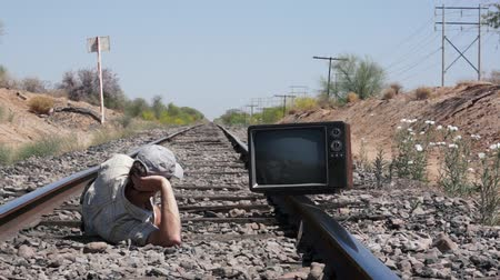 kamp : Man Laying on the Railway Tracks with an Old, Retro TV
