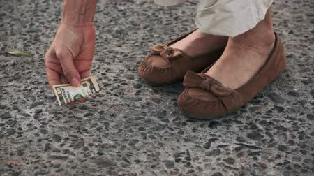cash free : Woman finds a lost 10 dollar bill on the street and picks it up.