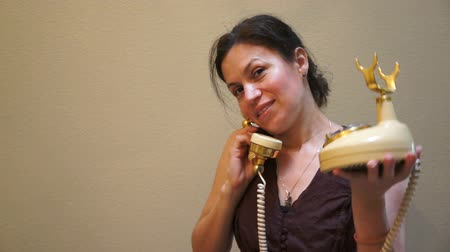 halkalar : Beautiful woman with a big, gorgeous smile using an old, retro style, antique telephone.
