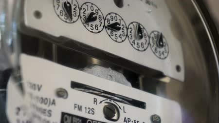 utilidade : Close up shot of a electrical utility meter used to measure the amount of electricity that is being used so the utility company can bill the customer for the kilowatt hours of electricity that theyve used. Stock Footage