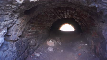 mroczne : Panning across the entrance of an old brick tunnel with a bright light at the end.
