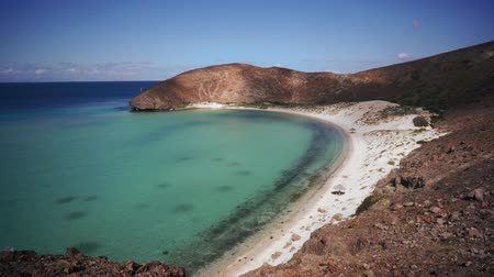 sandy waters : High angle, wide shot of an ocean bay with a white sandy beach and clear turquoise waters.