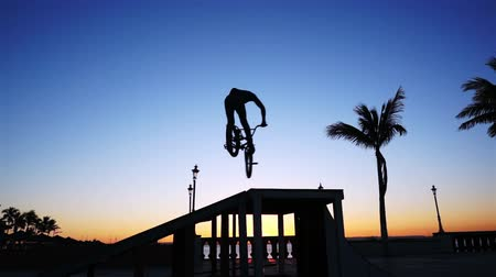 bmx : Low angle shot of the silhouette of a guy on a BMX bike doing a jump and a 360 degree spin in the air.