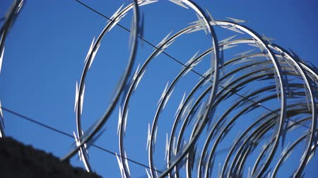 farpado : A close up, dolly shot of razor wire glistening in the sun against a blue sky. Stock Footage