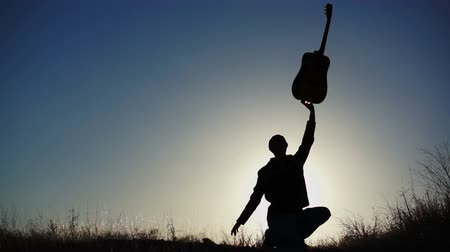 kytara : Silhouette of an artistic musician holding his guitar up in the air with one hand.