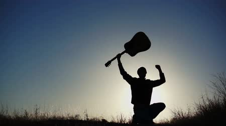 kytara : Silhouette of a musical performer holding his guitar up in the air and making a winning gesture.