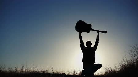 джаз : Silhouette of a musical performer holding his guitar up in the air and making a gesture of being proud.