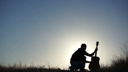 kytara : Silhouette of a performance artist twirling his guitar while its set on the ground.