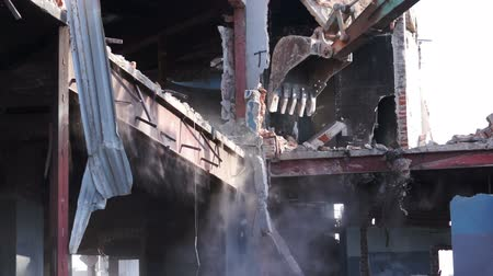 condemned building : Close up shot of a heavy equipment excavator being used to destroy an old, abandoned brick and concrete building with a steel sub-structure. Stock Footage