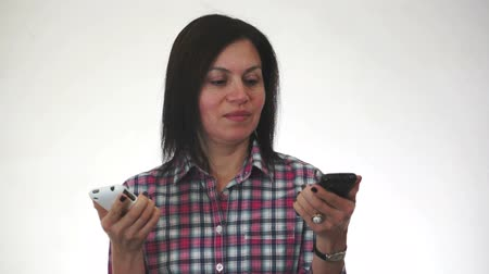 hívó : Woman with two cell phones looks at each one but doesnt take the calls and puts them together so that the callers can talk to each other. Stock mozgókép