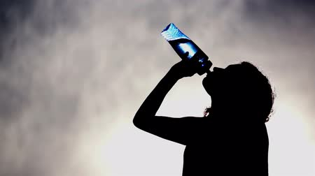 lifestyle : Silhouette of a woman drinking water out of a blue, translucent water bottle with a cloudy grey and blue sky background.
