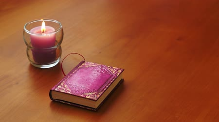 фиолетовый : A candle and a cute little, purple book sitting on a wooden table in a romantic setting.
