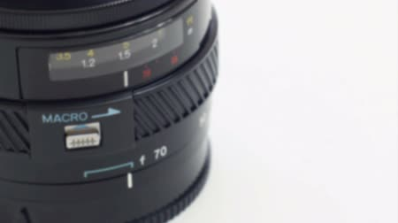 фокус : Slow rack focus into a camera lens with the word macro marked on it.
