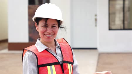 helmets : Close up of a middle aged, hispanic, female foreman or forewoman on the job-site and turning towards the viewer and smiling.