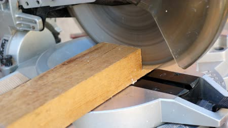 miter saw : Shallow depth of field shot, with no people or body parts entering the camera frame, of an industrial miter saw cutting wood.