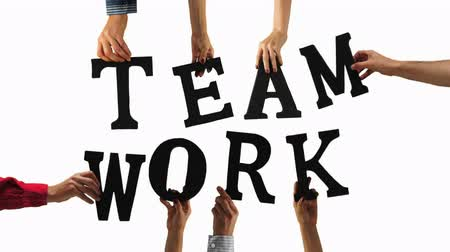 trabalho em equipe : Many peoples hands holding the letters that spell out the word TEAM WORK to signify a team of people working together to achieve their goal.