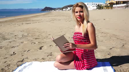 ruha : Girl on Beach in Sundress Reading Stock mozgókép