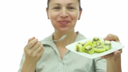 çatallar : Woman Eating Kiwi Fruit Off of Plate