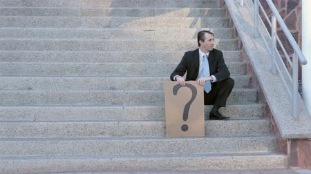 deski : Businessman on Steps with Question Mark Sign Wideo