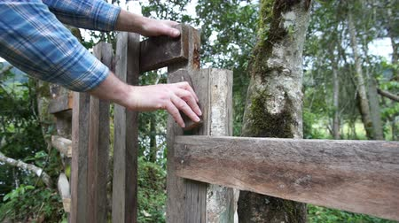 защелка : Anonymous man opening a rustic style gate in a fence along a trail in the wilderness among some trees. Стоковые видеозаписи
