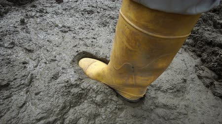 bahno : High angle close up shot of an anonymous person wearing a yellow rubber boot stepping into and almost getting stuck in deep and sticky mud. Dostupné videozáznamy