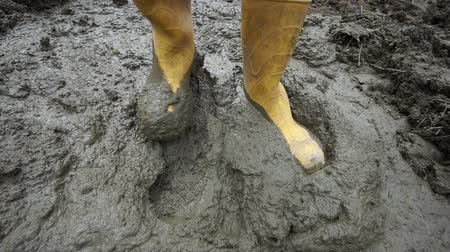 резина : Close up high angle shot of an anonymous person in yellow rubber boots stepping around in deep and sticky mud.