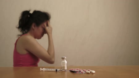 zihinsel : Dolly shot of a female figure in the background rubbing her head in pain or with depression and a syringe and pills in the foreground on the table.