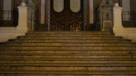 Эквадор : Tilt up shot of the stairs and entrance to a catholic church at night in Loja Ecuador.