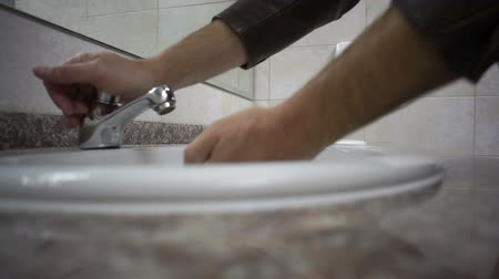 уборная : Close up shot of a man in a public washroom taking soap from the dispenser then trying to start the water tap that does not work and then moving to another to wash his hands.