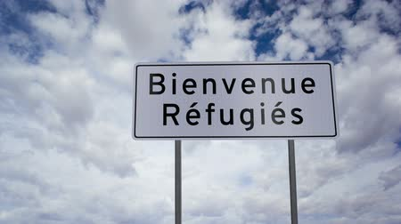 refuge crisis : Highway road sign with the words refugees welcome written on it in the French language with a time-lapse clouds background.
