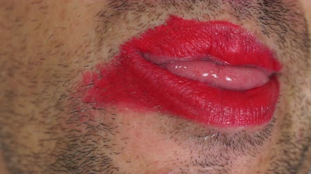 kapatmak : Close up shot of a strange male with whiskers on his unshaven face and lips covered with makeup making faces and weird movements with his lips and tongue. Stok Video
