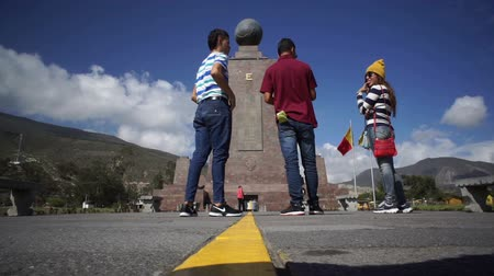 separação : QUITO, ECUADOR - JANUARY 5 2016: Timelapse shot of the Mitad del Mundo monument and tourists on the equator that separates the north and south hemispheres in Quito, Ecuador.