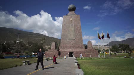 separação : QUITO, ECUADOR - JANUARY 5 2016: Handheld shot of the Mitad del Mundo monument and tourists on the equator that separates the north and south hemispheres in Quito, Ecuador.